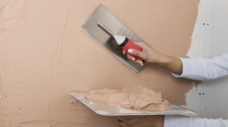 Plastering and applying skim coat to walls