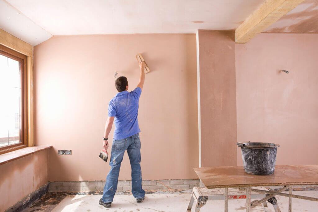 plasterer working on plastering full walls and ceiling