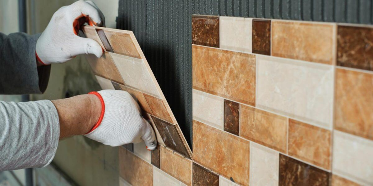 Tradesman tiling a wall in a London home